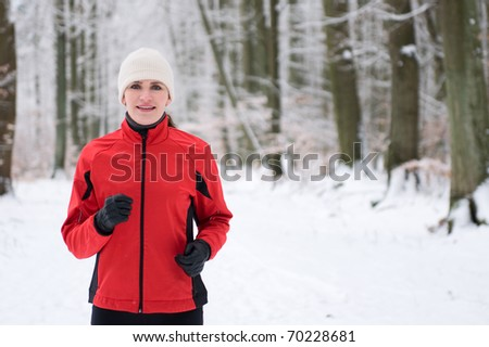Woman running in winter forest