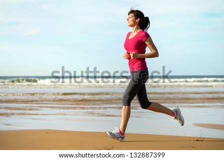 Woman running on beach at sunset. Beautiful fitness caucasian girl exercising outdoors on sea background. Caucasian fit model.