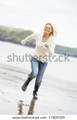 Woman running on beach smiling