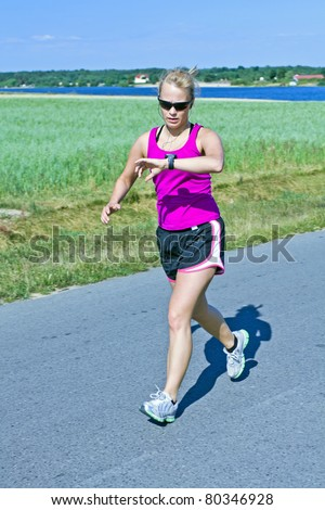 Woman running on country road, checking a watch heart rate monitor and listen to music. Training and exercising in summer nature beautiful outdoors