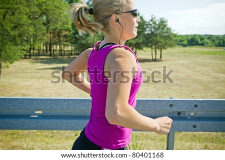Woman running on country road in summer nature, motion blur