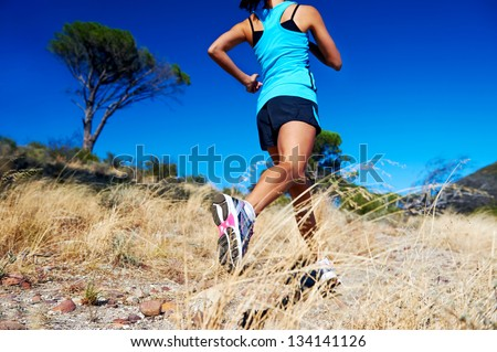 woman running on nature trail sunny day blue sky and jumping athlete