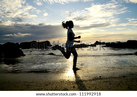Woman running on the beach silhouetted the sunrise.