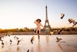Woman running on the famous square dispersing pigeons with great view on the Eiffel tower early in the morning in Paris