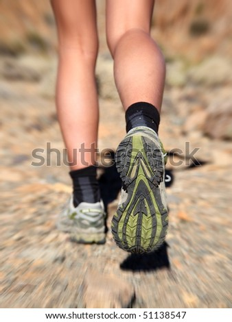 Woman running on trail in desert. Zoom motion blurred closeup shoes of woman trail running in desert.