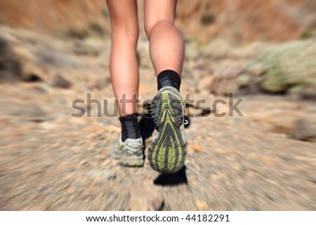 Woman running on trail. Zoom motion blurred closeup of woman trail running in desert on the volcano Teide, Tenerife.