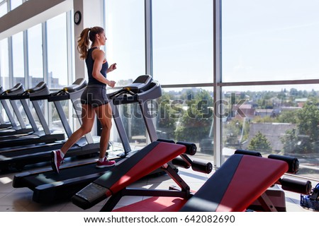 Woman running on treadmill at a panoramic window and listening to music via headphone at gym. Concept of healthy lifestyle.