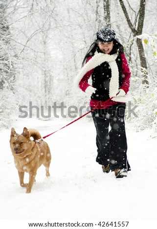 Woman running with dog during snow fall
