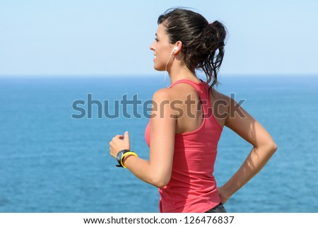 Woman running with earphones on sea background. Caucasian beautiful fitness girl working out on summer. Copyspace.
