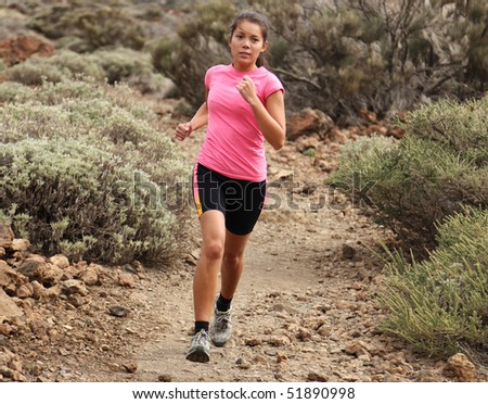 Woman running. Woman trail running outdoors on dirt single track in desert landscape in cross country running shoes.
