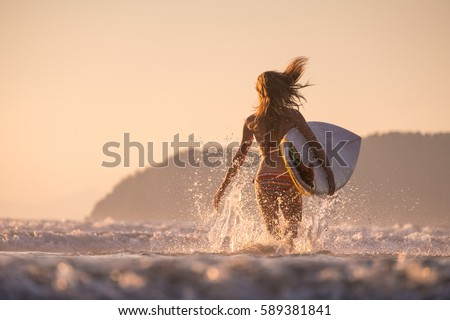 Woman runs into the ocean with surfboard