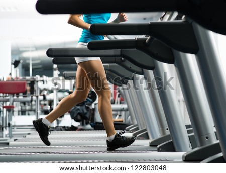 woman runs on a treadmill, exercise in the sport club