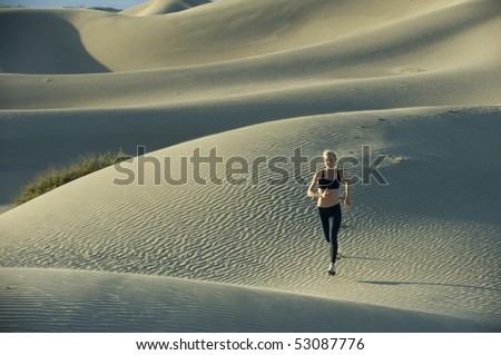 Woman runs on sand dunes.