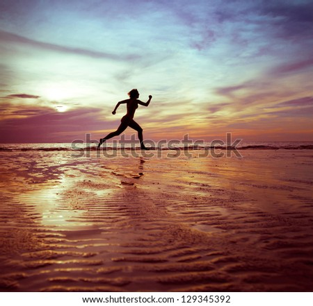 woman runs, silhouette on the beach at sunset