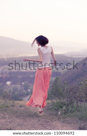 Woman runs up the hill at sunset