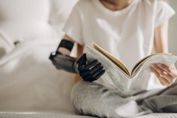 woman's artificial arm holding a book, close up photo. blurred image.normal life with a prosthetic limb