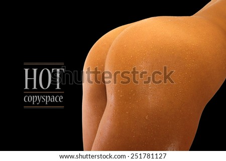 Woman\'s back and hips with contrast lighting and black background with copy space