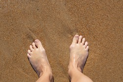 woman's bare feet on the yellow sand. Summer rest. A large bone on the toe of the right foot.
