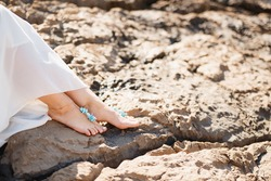 Woman's bare feet with elegant pedicure and bracelets on the rocks, close-up. Woman sitting on the rocky beach