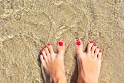 Woman's bare feet with red nails at the transparent sea water with golden sand, selective focus. Bare feet in a sea wave on the beach. Relaxation in the ocean.  Woman toes with pedicure. Summertime.
