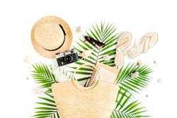 Woman's beach accessories: rattan bag, straw hat, tropical palm leaves on white background. The concept of travel. Summer background. Flat lay, top view.