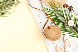 Woman's beach accessories:  rattan bag, straw hat, tropical palm leaves on yellow background. Summer background. Flat lay, top view.