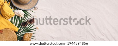Woman's beach accessories: swimsuit, bikini, rattan bag, straw hat, shells, sunglasses, palm leaves on sand background. Exotic, tropical mood. Summer vacation, travel concept. Flat lay. Copy space. Foto stock ©