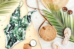 Woman's beach accessories: swimsuit with tropical print, rattan bag, straw hat, tropical palm leaves on yellow background. Summer background. Flat lay, top view.