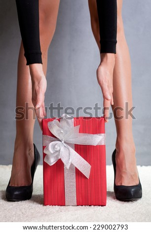 Woman\'s beautiful sexy legs and  Christmas red gift box with silver ribbon and bow