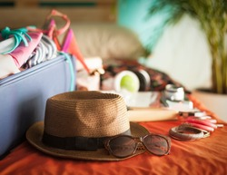 Woman's bedroom full of things ready to be taken on summer holiday.