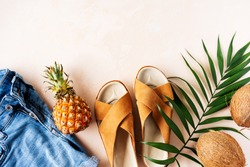 Woman's casual trendy leather sandals with crisscross details and denim shorts for summer vacation outfits on pink pastel background with palm leaf. Long wide banner.