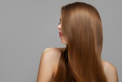 Woman's clean styled hair. Half of the face is covered with brunette hair