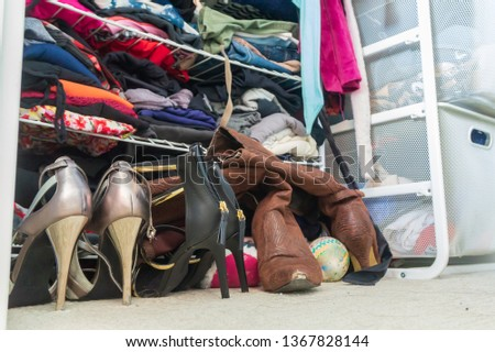 Woman's closet with high heel shoes, stacked, folded clothes on shelves and part of robes hanging. Depicting closet organization, time to donate clothes, fashion lifestyle, consumerism, etc.