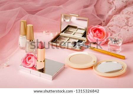 Woman's cosmetics on romantic pink lacy tulle background. Women's morning secrets. Cosmetics, lipstick,perfume, brush, powder, highlighter, concealer,patelle with eye shadows. Female cosmetics.Make up #1315326842
