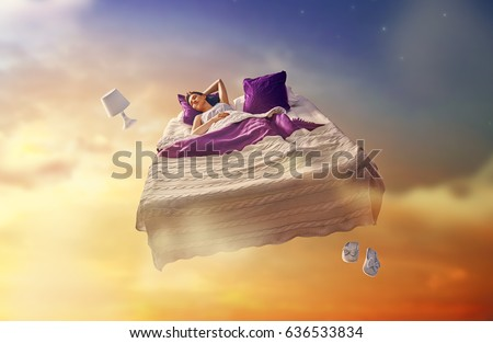 Woman's dreams. Pretty girl is flying in her bed trough star sky.