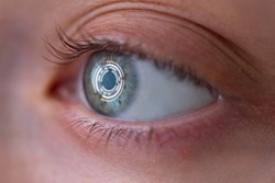 Woman's eye with smart contact lens with digital and biometric implants to scan the ocular retina close up. Concept of future and technology for digital scans