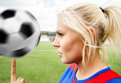 woman's face against green grass field, sky and stadium. football girl wear uniform and turn on finger white and black ball.