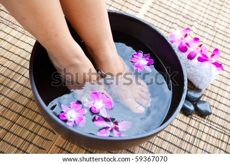 Woman's feet in foot spa bowl with orchids