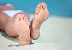 Woman's feet on the white sand near the sea.