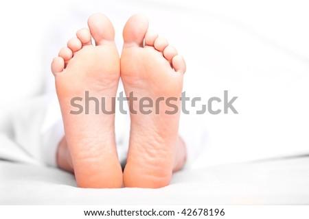 Woman's feet under the blanket. Soft Focus.