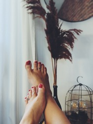 Woman's feet with a pedicure, nail polish and toe rings