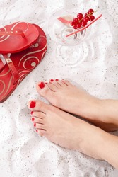 Woman's feet with red toenails in the sand