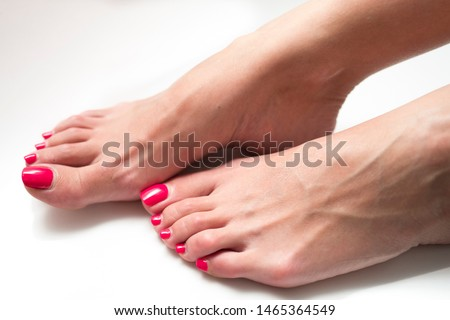 Woman's feets with a red nails isolated on white background.
