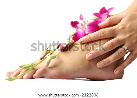 Woman's foot and hand on white with orchid flowers