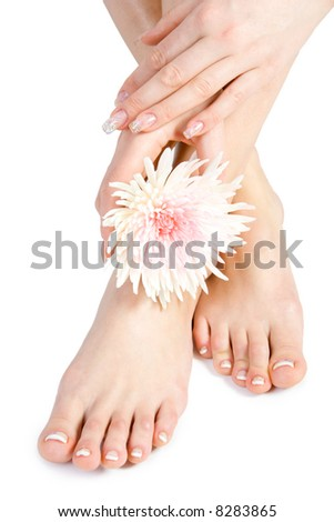 Woman's foot and hand with flowers isolate on white