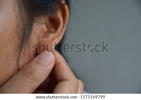 Woman's hand catches the lobe to show half face