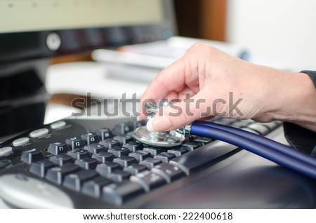 Woman\'s hand checking a keyboard with a stethoscope, closeup
