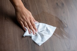 Woman's hand cleaning home office table surface with wet wipes
