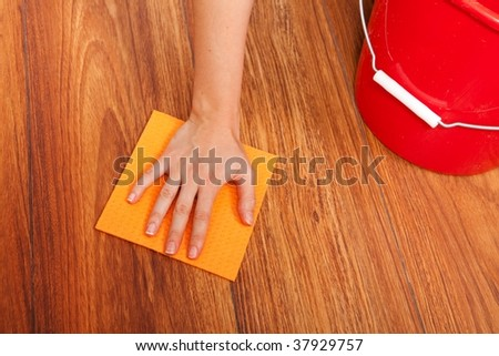Woman's hand cleaning the floor with yellow sponge
