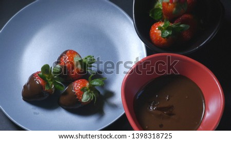 Woman's hand dips strawberry into chocolate mixture and puts it on the plate #1398318725